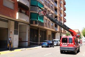 Els Bombers de la Generalitat inspeccionant amb un camió grua l'habitatge del carrer Girona de Lleida