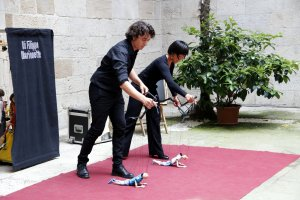 Imatge dels dos components de la companyia Di Filippo Marionette fent ballar titelles al pati de l'IEI durant l'espectacle 'Appeso ad un Filo'