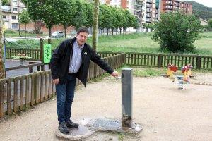 Pla general de l'alcalde Oliana, Miquel Sala, fent córrer l'aigua d'una font del municipi
