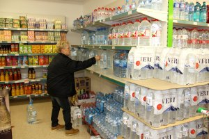 Pla general d'una persona comprant aigua embotellada en un supermercat d'Oliana