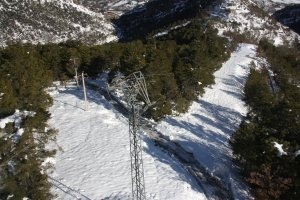 Pla general d'una torre elèctrica, vista des d'un helicòpter, malmesa per la nevada caiguda aquest dilluns a l'Alt Urgell