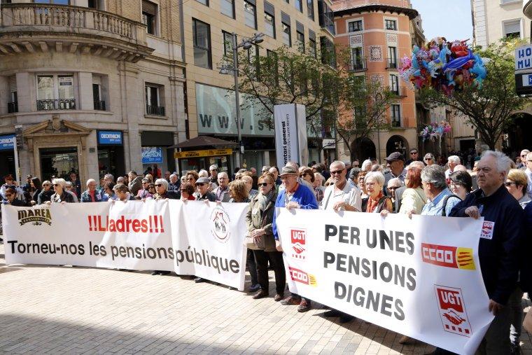Imatge general dels pensionistes concentrats a l'entrada de la plaça Sant Joan de Lleida, amb les pancartes