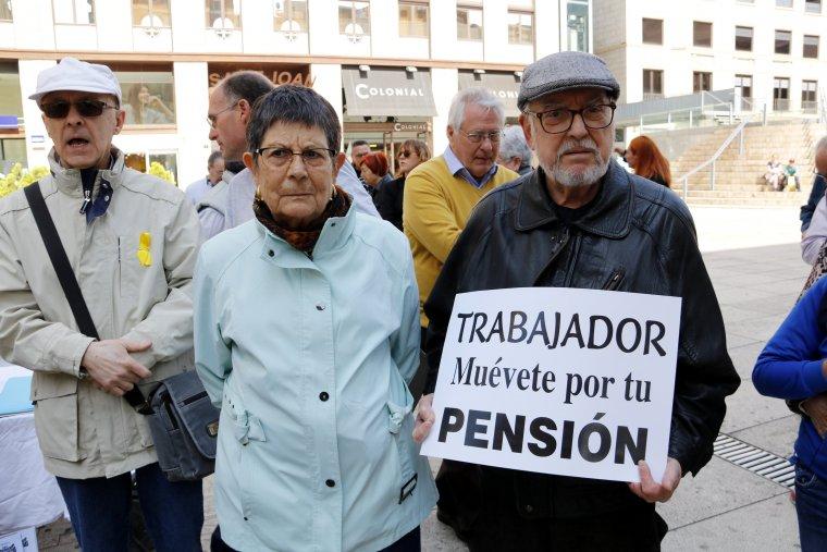Pla mig de dos jubilats, un dels quals sosté un cartell