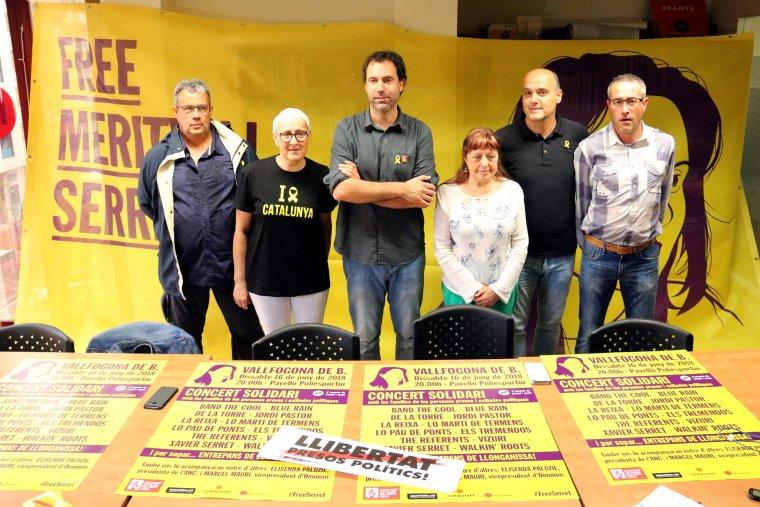 Representants de l'organització a la seu d'Òmnium Cultural a Lleida, amb una gran pancarta del concert #FreeSerret