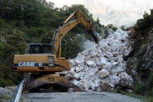 Pla general on es pot veure una màquina esmicolant la roca de grans dimensions que ha caigut a la carretera L-913