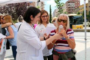 Pla mig d'una dona que es fa la prova del monòxid de carboni amb dues sanitàries a la parada informativa contra el Tabaquisme