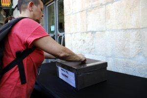 Pla mig d'una persona dipositant diners a la caixa solidaria per recollir fons per repatriar al Senegal el cos del nen