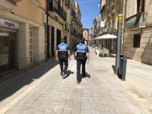 Pla sencer de dos agents de la Policia Local de les Borges Blanques, d'esquenes, patrullant pel municipi