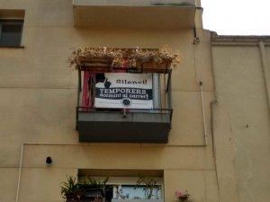 Un balcó del Centre Històric de Lleida mostra una pancarta per denunciar la situació dels temporers que dormen al carrer