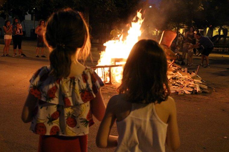 Dues nenes contemplen una foguera a la plaça de la Creu Alta de Sabadell