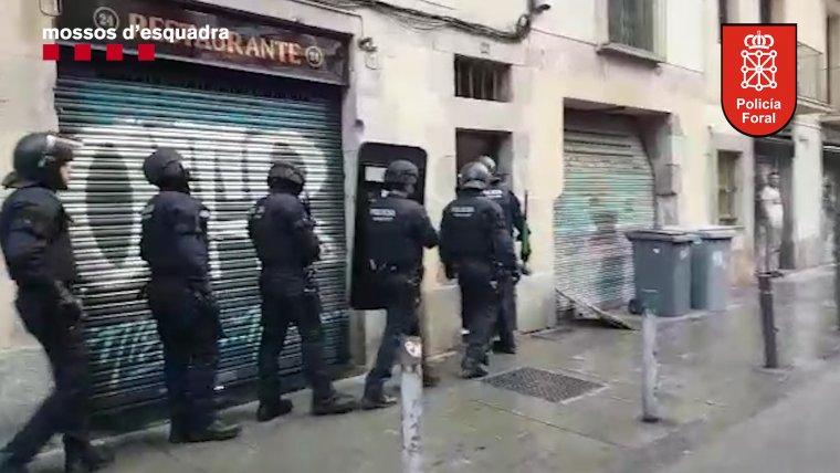 Sis mossos d'esquadra entrant en un dels domicilis de Lleida on s'amagava el grup especialitzat