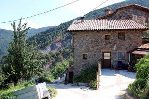 Imatge d'una casa del poble de Mencui i l'esllavissada de la muntanya al fons