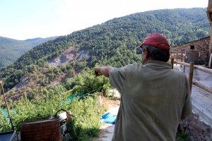 Un veí de Mencui mostra una esllavissada a la muntanya prop del poble