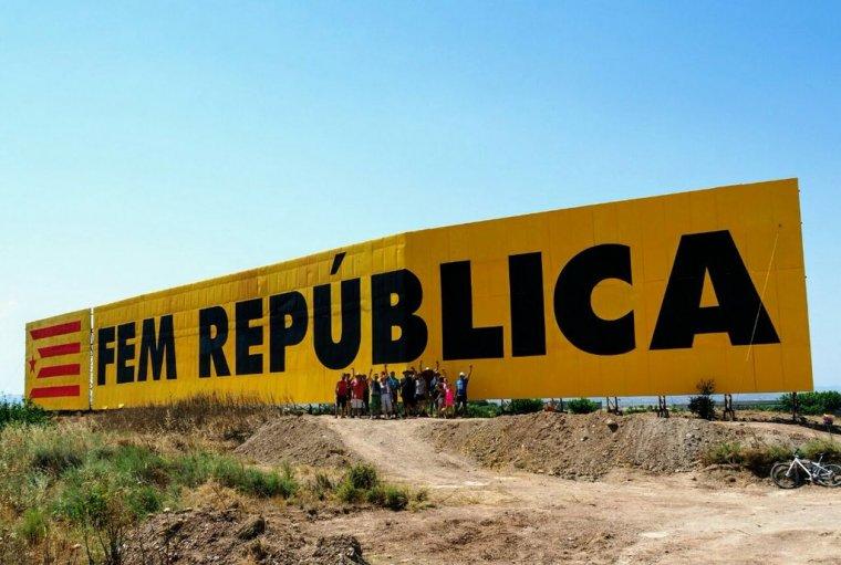 El mural independentista repintat a Bellpuig i els voluntaris participants.