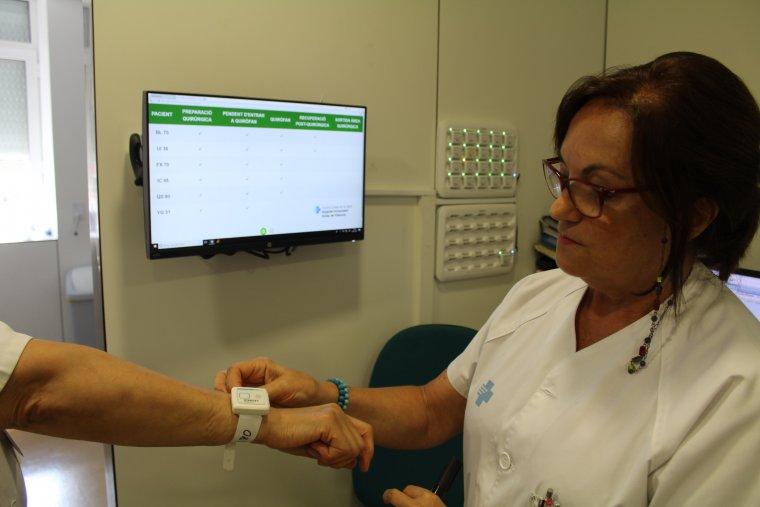 Una infermera col·locant la polsera