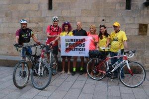 Els tres ciclistes, amb altres persones que els acompanyaven, mostrant una pancarta reclamant l'alliberament dels presos, abans d'iniciar la pedalada a la plaça Paeria