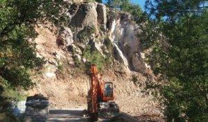 Pla general on es veu una màquina que està duent a terme obres a la carretera d'accés a Torà de Tost