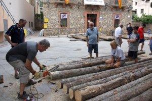 Pla general on es veu una persona preparant un dels troncs que es farà servir per construir els rais