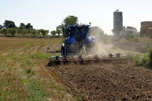 Pla obert on es pot veure un tractor llaurant un camp a la Ribera d'Ondara