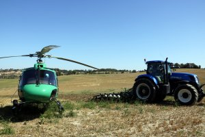 Pla obert on es pot veure un tractor llaurant un camp de cereal ja segat al costat de l'helicòpter dels Agents Rurals