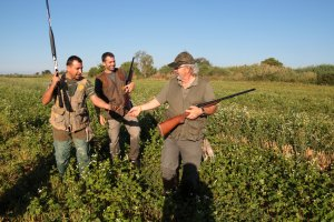 Un grup de caçadors mostrant una guatlla abatuda en el primer dia del període de la mitja veda de caça