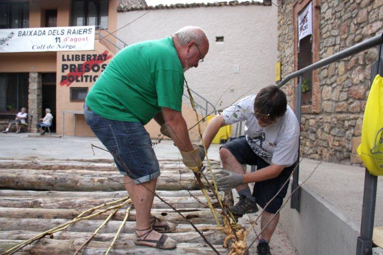 Dues persones treballant en la unió dels troncs, amb branques de bedoll, que conformen un dels trams que s'utilitzarà per fer un rai per a la 29a Baixada dels Raiers