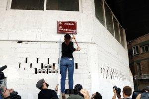 Imatge del moment que la portaveu de la Plataforma Lleida Lliure de Franquisme Rosa Peñafiel arrenca la placa del carrer Alcalde Areny