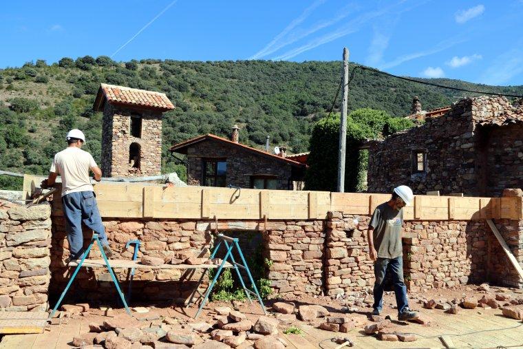 Imatge de dos operaris treballant en la construcció d'un equipament al poble d'Envall