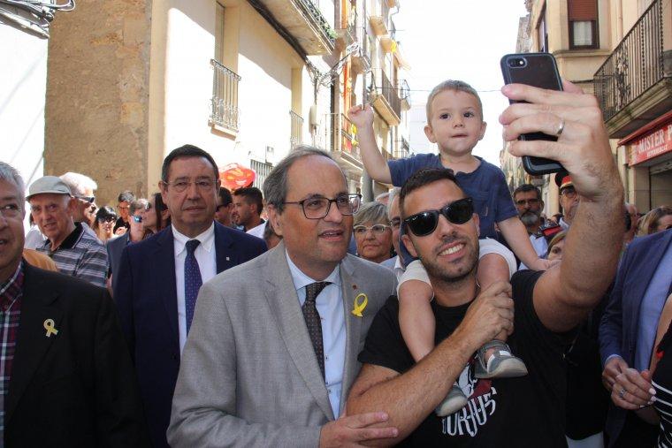 Pla mig del president de la Generalitat, Quim Torra, fent-se una 'selfie' amb un veí