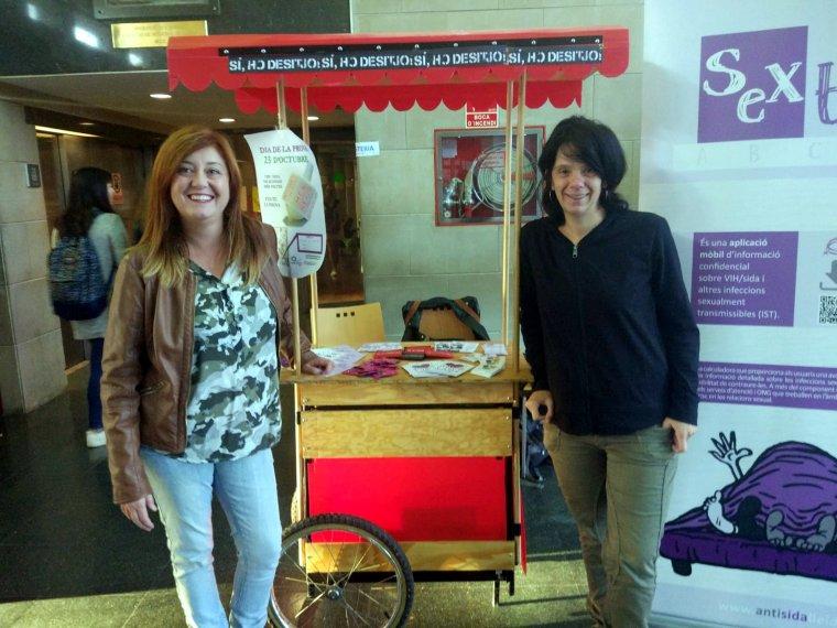 Dues voluntàries en una de les taules informatives instal·lades per l'Associació Antisida de Lleida a la UdL