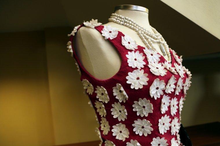 Imatge detall d'un vestit de paper vermell amb flors blanques