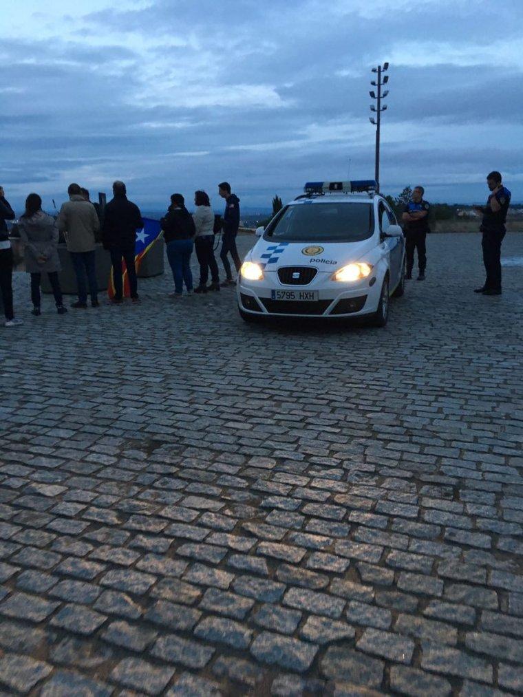 Pla obert on es pot veure un cotxe de la Guàrdia Urbana al costat dels membres d'ERC