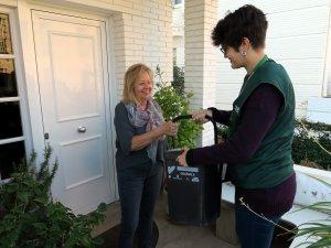 Una educadora ambiental lliura a una veïna un kit per a la recollida selectiva de residus