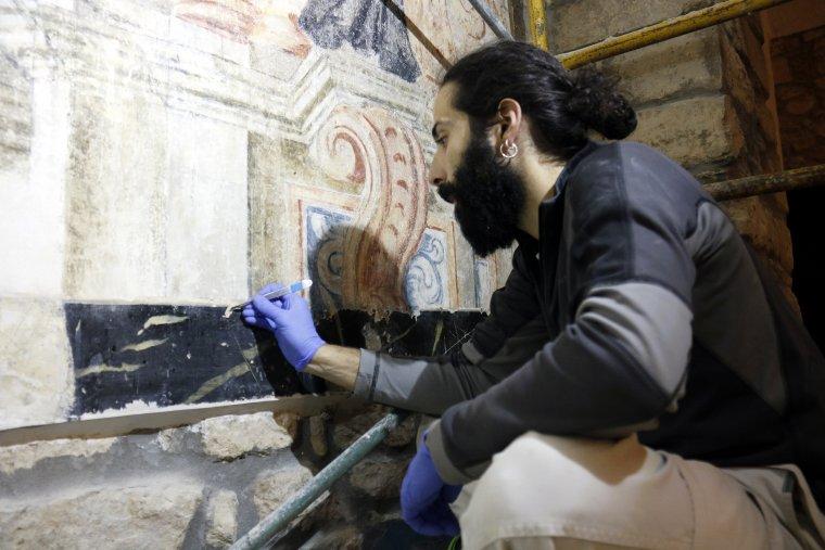 Pla mitjà on es pot veure un restaurador treballant en les pintures barroques de l'eglésia de Butsènit