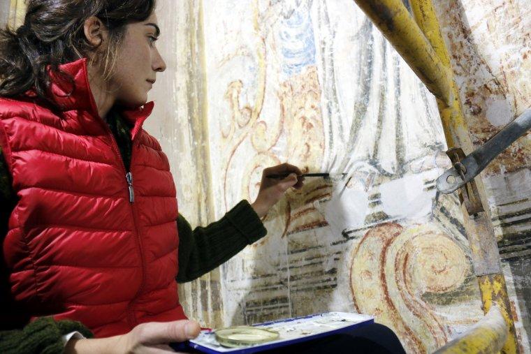 Pla mitjà on es pot veure una restauradora treballant en el retaule barroc de l'església