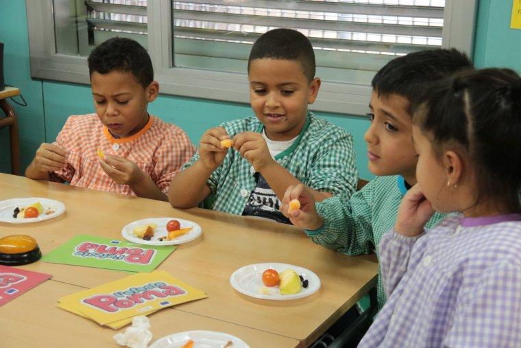 Alumnes de l'escola Camps Elisis de Lleida menjant fruita dins un taller