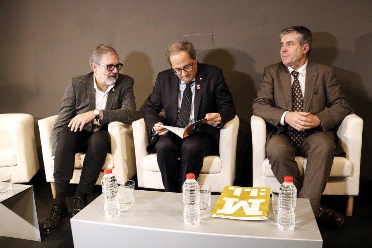 El president de la Generalitat, Quim Torra, mirant el llibre 'Operació Trasllat', acompanyat del director del Museu, Josep Giralt (dreta) i l'alcalde de Lleida, Fèlix Larrosa