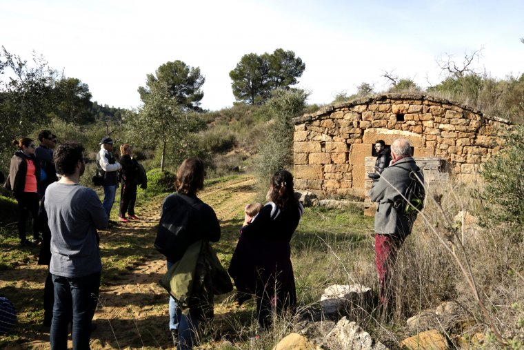 Imatge del grup de visitants, davant una cabana de volta