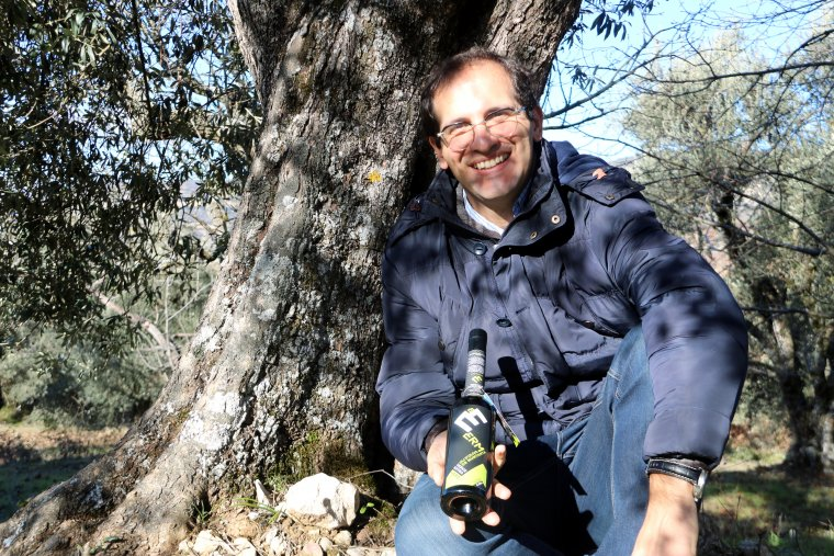Ivan Caelles, productor de l'oli Erm, mostra una ampolla al peu d'una olivera