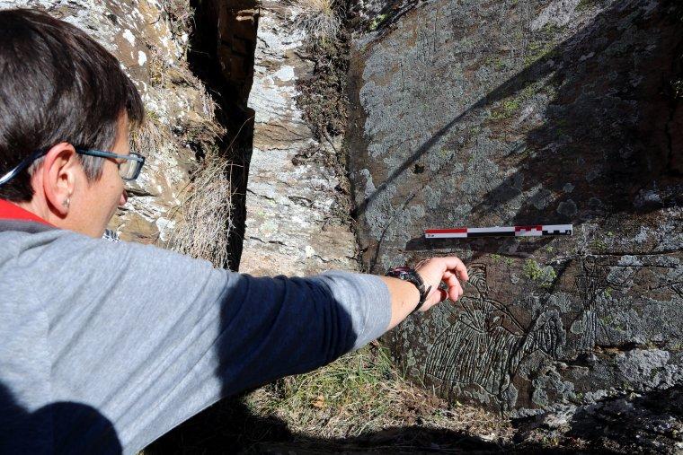 Una persona assenyala amb la mà un dels gravats a la roca
