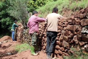Persones reparant un tros de paret de pedra seca a la ruta del Cinquè Llac