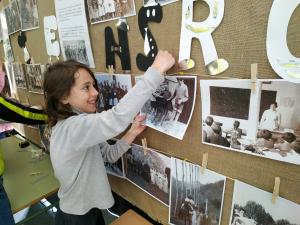 Pla mig d'una nena penjant una fotografia en un mural