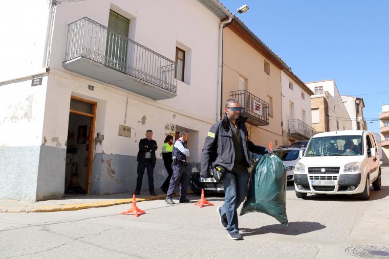 Un Mosso treu de la casa dels detinguts una bossa plena