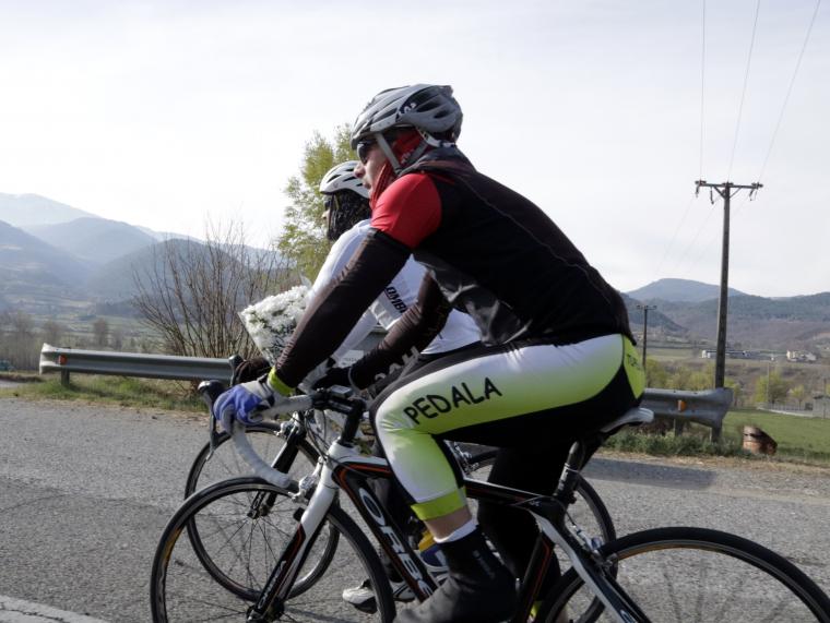 Imatge de dos ciclistes, un d'ells porta un ram de flors