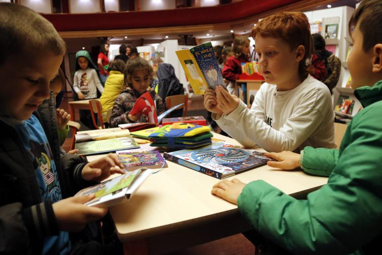 Pla mitjà on es poden veure diversos escolars llegint al 35è Saló del Llibre Infantil