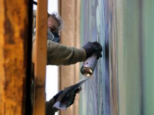 Imatge picada d'un dels artistes murals pintant en una de les parets del municipi