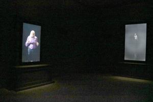 Pla general on es poden veure dues pantalles amb fragments audiovisuals de l'obra