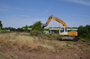 Pla obert on es pot veure una màquina treballant en els terrenys