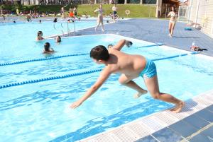 Un nen llençant-se a la piscina