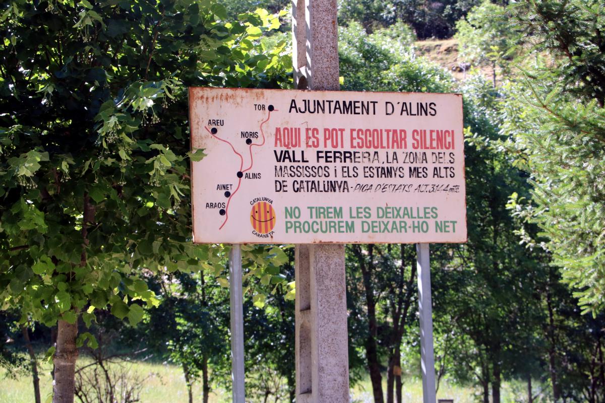 """Pla general d'un cartell on s'hi pot llegir """"Aquí es pot escoltar silenci"""" al poble d'Alins"""